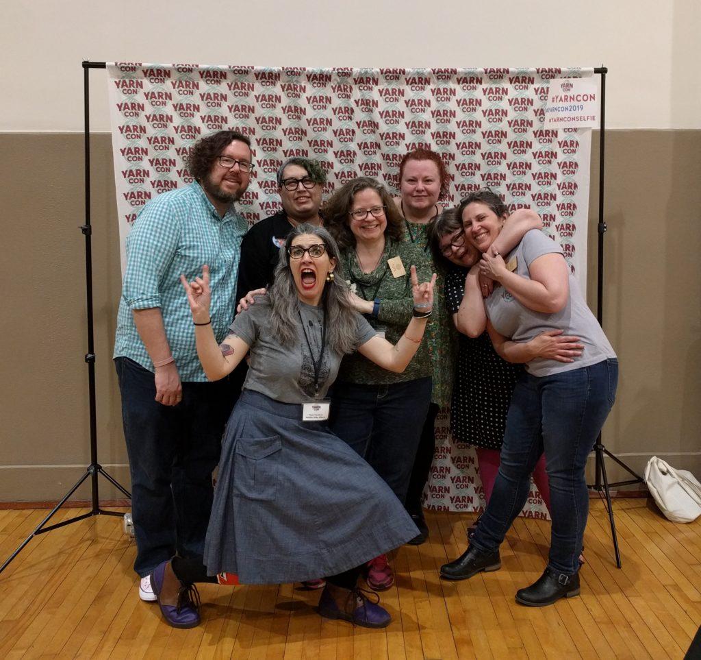 Team YarnCon posing in front of the YarnCon Selfie Station